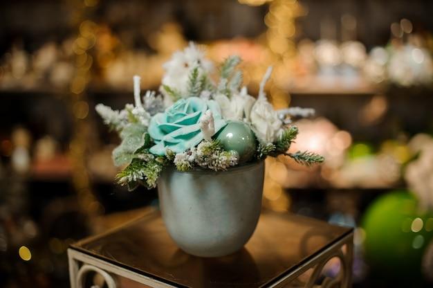 Vaso con composizione di decorazioni natalizie di rami di abete, fiori blu e ornamenti a palla