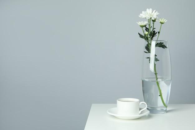 Vaso con crisantemi e tazza di caffè sul tavolo bianco.