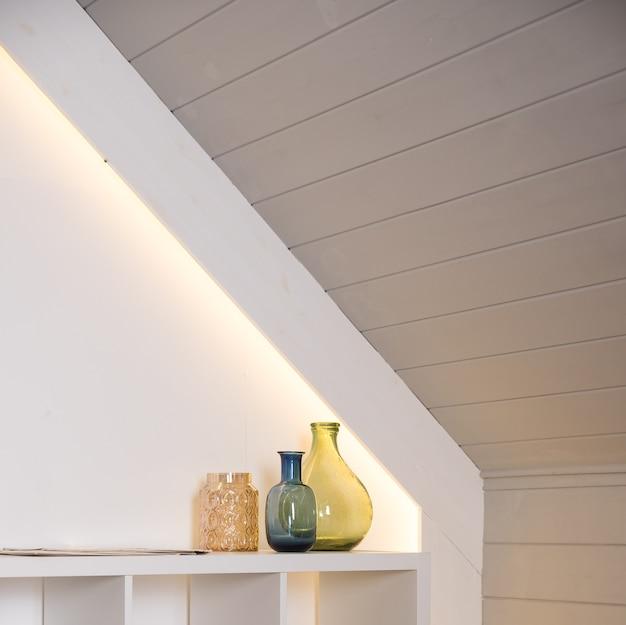 Un vaso con fiori secchi e bottiglie d'oro e decorazioni sul tavolo sullo sfondo di un muro chiaro. stile moderno di decorazione d'interni. decorazioni per la casa con bottiglie di vetro colorate