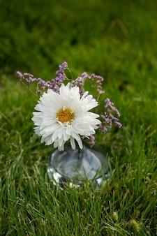 Vaso con un fiore sull'erba verde