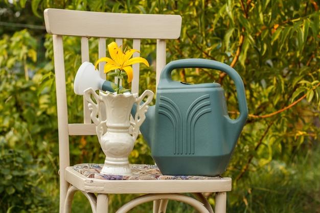 Vaso con fiore di giglio e sedia vecchia cannone annaffiatoio in sfondo naturale. giardino in giorno d'estate. Foto Premium
