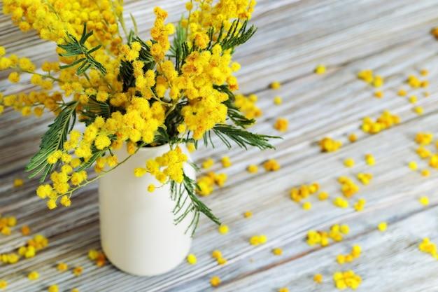 Vaso con fiori di mimosa su tavola in legno rustico