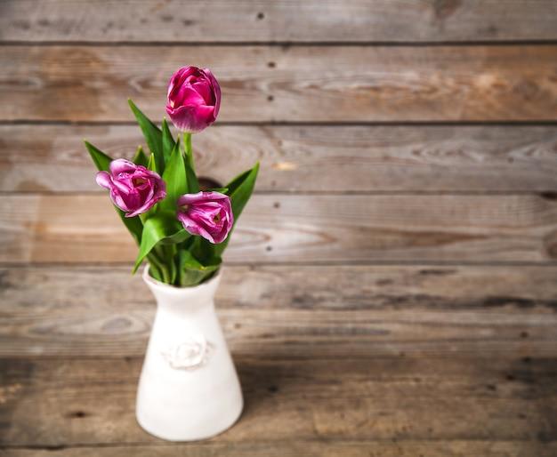 Vaso con tulipani naturali su un tavolo di legno