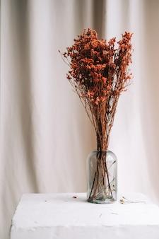 Vaso con fiori secchi rossi su un tavolo bianco su tessuto di raso