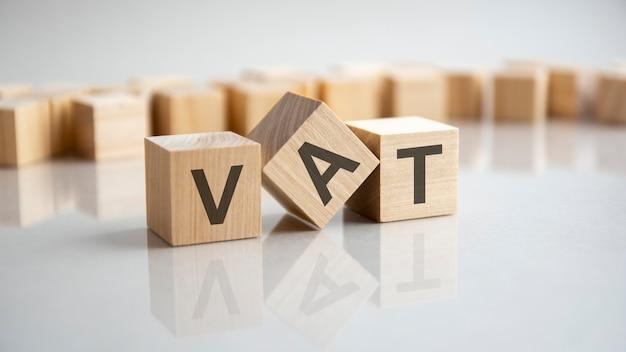 Iva - imposta sul valore aggiunto acronimo concetto su cubi, sfondo grigio. riflessione sulla superficie specchiata del tavolo. messa a fuoco selettiva.