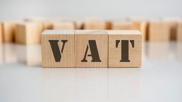 La parola iva è composta da blocchi di legno che giacciono sul tavolo grigio, concetto.