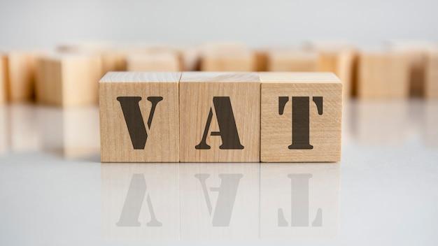 Parola iva scritta su blocco di legno. la parola iva è composta da blocchi di legno che si trovano sul tavolo grigio, concetto di business.