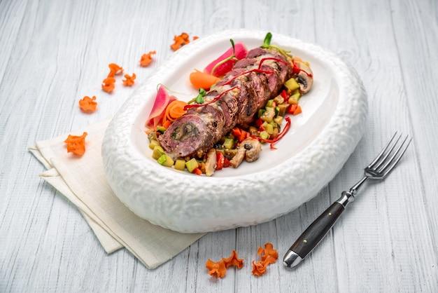 Involtino di vitello ripieno di funghi con spezzatino di verdure. sul tavolo di legno
