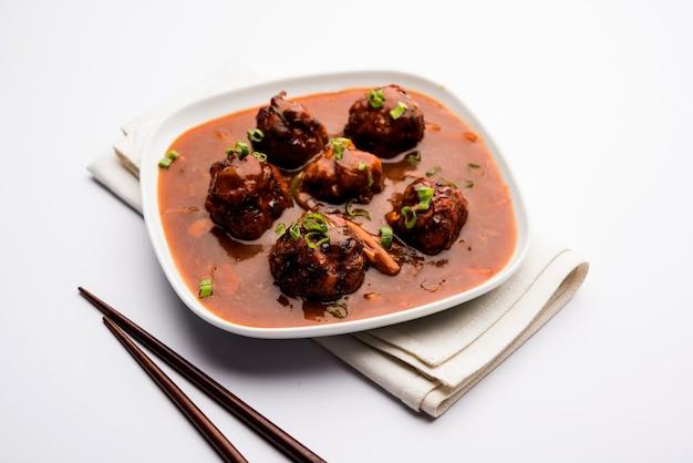 Veg o pollo manchurian con sugo - cibo popolare dell'india servito in una ciotola con bacchette