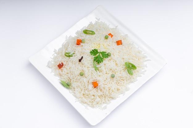 Veg pulao a base di riso basmati verdure e spezie disposte in stoviglie bianche quadrate