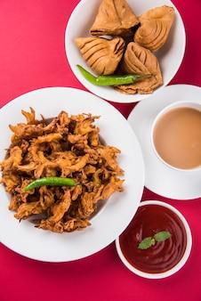 Veg samosa - è uno snack indiano croccante e speziato a forma di triangolo per l'ora del tè. servito con peperoncino verde fritto, cipolla e chutney o ketchup. su sfondo colorato o in legno. messa a fuoco selettiva