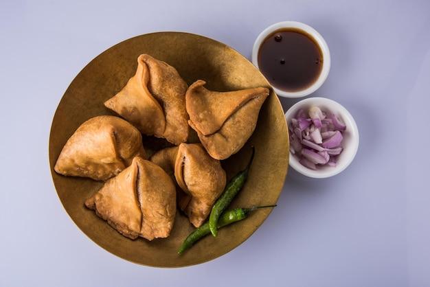 Veg samosa - è uno snack indiano croccante e speziato a forma di triangolo per l'ora del tè servito con peperoncino verde fritto, cipolla e chutney o ketchup