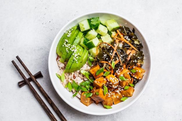 Ciotola vegana ahi poke con tofu, riso, alghe, avocado e cetriolo, sfondo bianco, vista dall'alto.