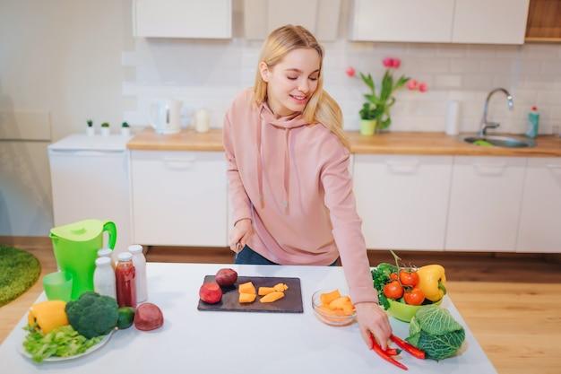Vegan bella donna bionda che cucina verdure colorate crude in cucina. dieta di cibi crudi. cibo vegetariano. mangiare sano