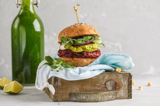 Hamburger vegano di barbabietola con verdure, guacamole e panino di segale con frullato verde.