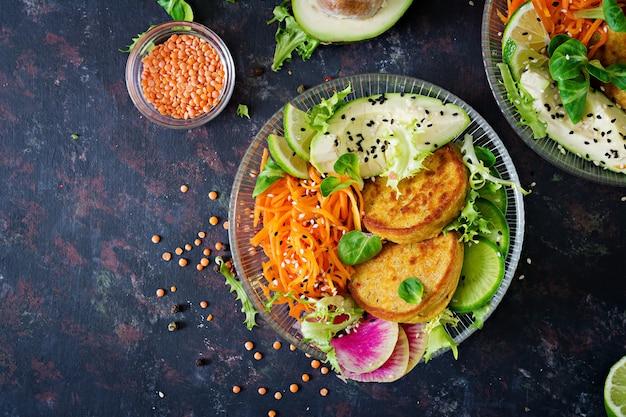 Tavola dell'alimento della cena della ciotola di buddha del vegano. cibo salutare. ciotola da pranzo vegana sana. frittella con lenticchie e ravanello, avocado, insalata di carote. disteso. vista dall'alto