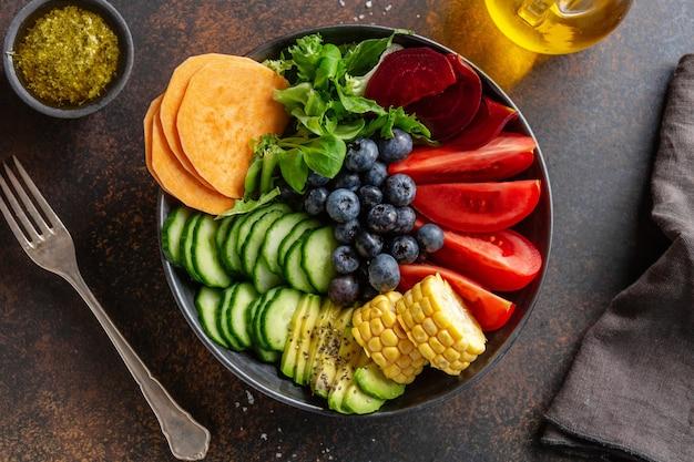Ciotola di buddha vegana con frutta e verdura servita in una ciotola su sfondo grigio. avvicinamento