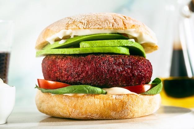 Hamburger vegano senza carne con avocado, pomodori e spinaci sul tavolo e vino rosso in un bicchiere
