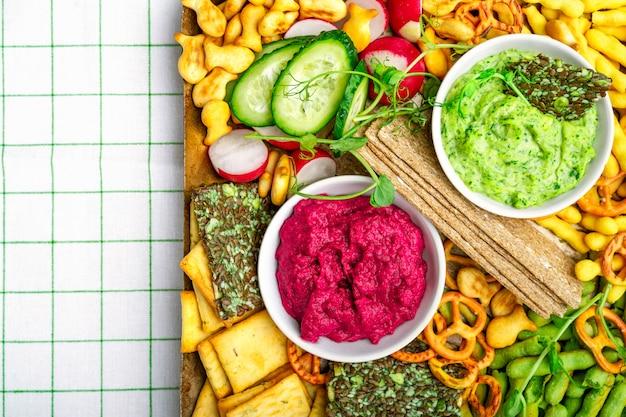 Salumi vegani con rape rosse e hummus di piselli, vari cracker, verdure fresche. vista del primo piano,