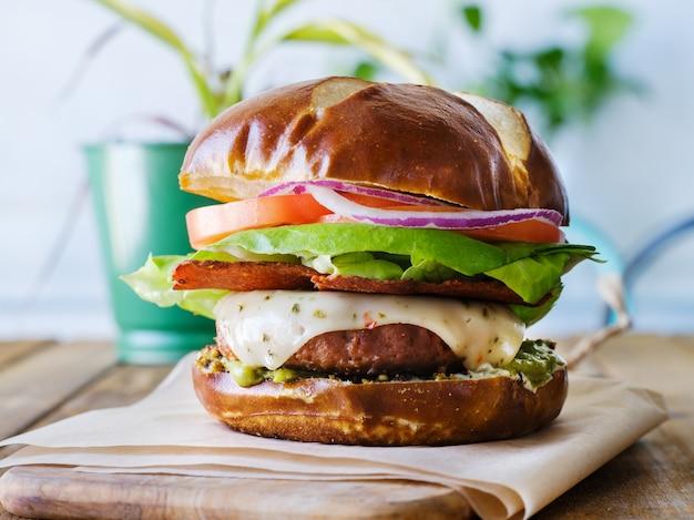Hamburger di formaggio vegano su panino pretzal e pancetta senza carne