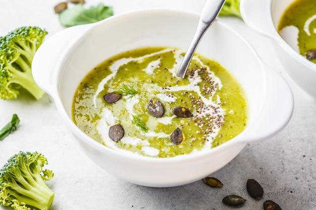 Zuppa vegana di crema di broccoli detox con crema di cocco e semi di zucca in una ciotola bianca. concetto di cibo a base vegetale.