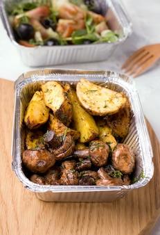 Consegna di cibo vegano. patate fritte con funghi