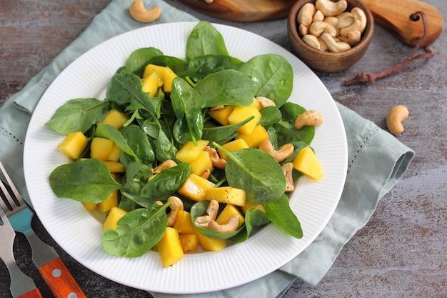 Cibo vegano insalata salutare con spinaci e mango pecan