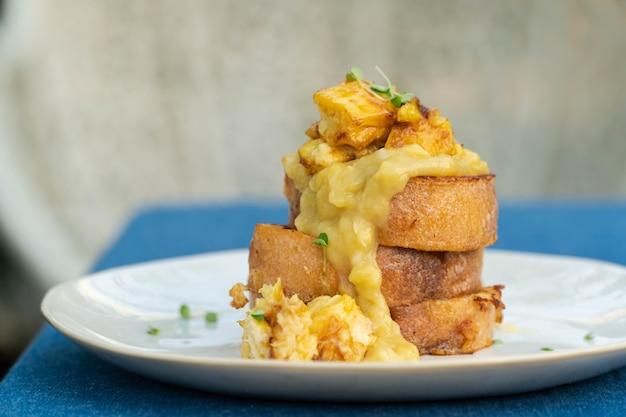 Toast francesi vegani con burro di arachidi, sciroppo e banana su un piatto bianco.