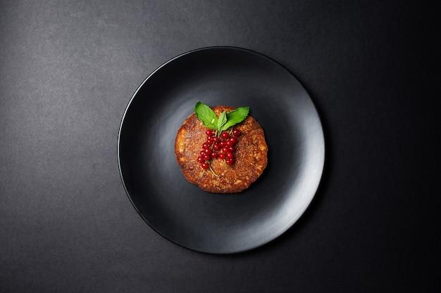 Pancake vegano fatto in casa con ribes rosso sul piatto, su sfondo nero.