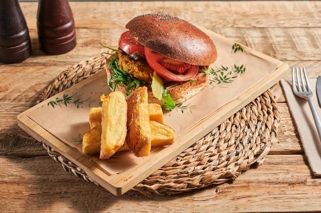 Hamburger di lenticchie vegano con patatine fritte sul tavolo di legno pronto da mangiare