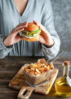 Hamburger di lenticchie vegane nelle mani di womam, con insalata e salsa di yogurt su sfondo bianco. concetto di cibo a base vegetale.