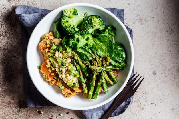 Ciotola da pranzo vegana con quinoa, broccoli, asparagi e salsa di funghi in ciotola bianca.