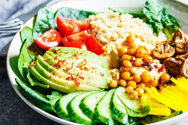 Ciotola pranzo vegana con quinoa, hummus, ceci, avocado, verdure e funghi. insalata di quinoa con verdure e hummus.