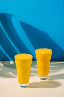 Frullato vegano di mango e cocco copia spazio sfondo beige e blu