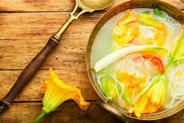 Zuppa di noodles vegana con fiori di zucca