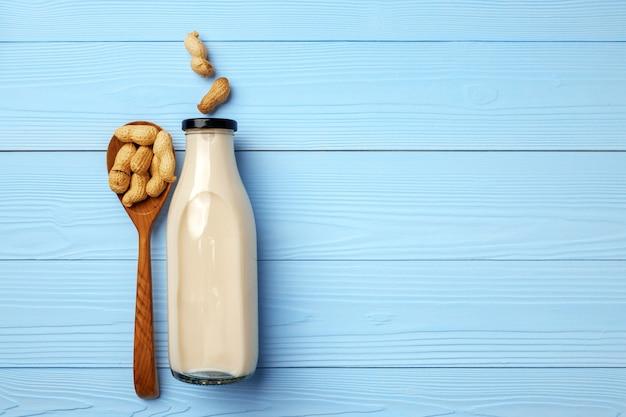 Latte di arachidi vegano in bottiglia di vetro con arachidi su tavola di legno