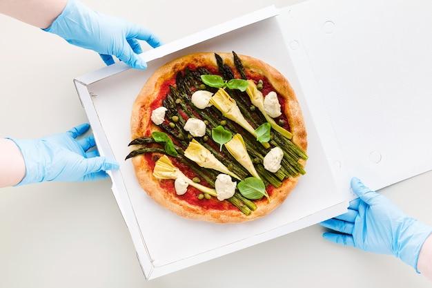 Pizza vegana con asparagi in una scatola per consegna, pubblicità o menu e mani in guanti chirurgici per la quarantena