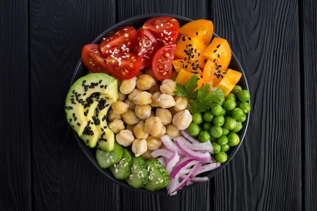 Poke bowl vegano con ceci e verdure nella ciotola scura