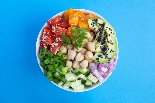 Poke bowl vegano con ceci e verdure nella ciotola bianca al centro