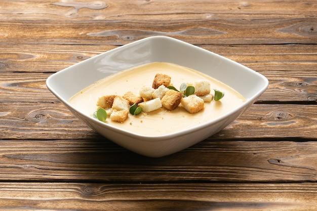 Crema di zucca vegana con crostini di pane in un piatto di ceramica bianca