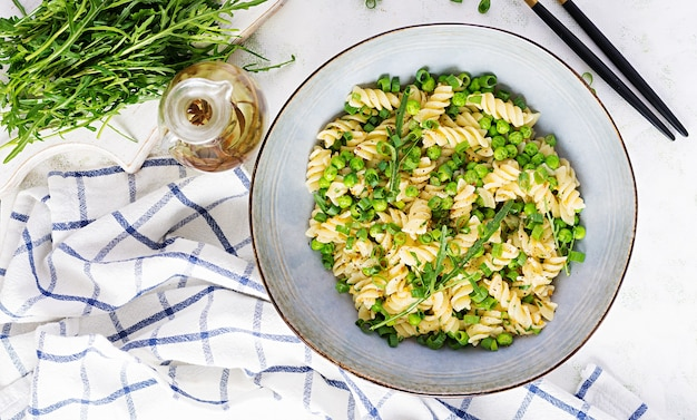 Insalata vegana. fusilli con piselli e cipolle. cibo italiano. vista dall'alto. lay piatto.