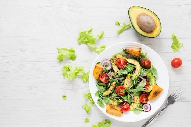 Insalata vegana con avocado sul tavolo di legno bianco