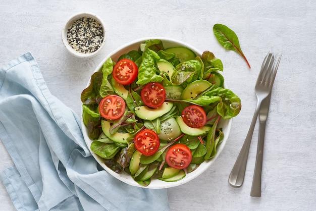 Insalata vegana con pomodori, cetrioli, avocado sul tavolo di cemento grigio pastello. cucina mediterranea vegetariana, pasto dietetico a basso contenuto calorico