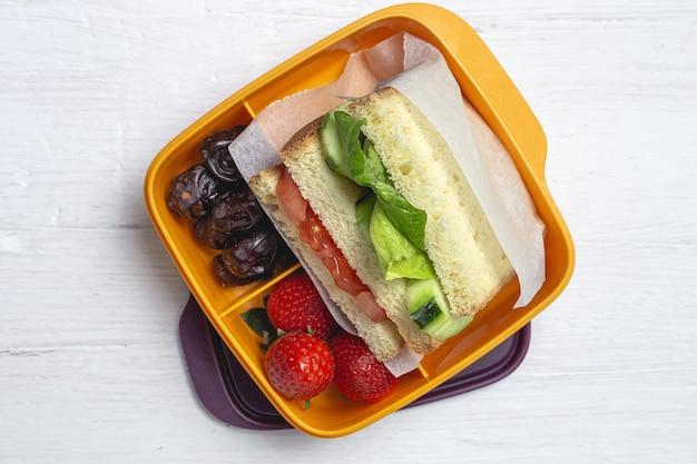 Vegan sandwich in un contenitore di plastica su sfondo di legno. concetto di cibo sano