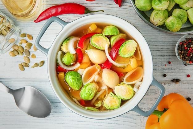 Zuppa vegana con cavolini di bruxelles in ciotola su tavola di legno