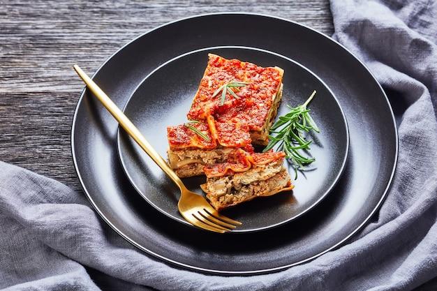 Lasagne vegane agli spinaci al tofu con champignon e pomodoro vegan bolognese e condimento italiano servito su un piatto nero con forchetta e rosmarino fresco su un tavolo di legno rustico scuro, primo piano