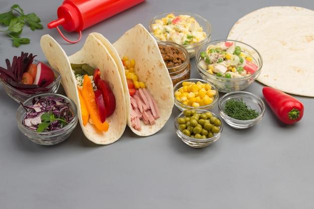 Tortilla vegana avvolge con insalata e verdure varie.