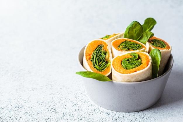 Tortilla vegana avvolge con patate dolci e spinaci. concetto di cibo vegetariano sano.