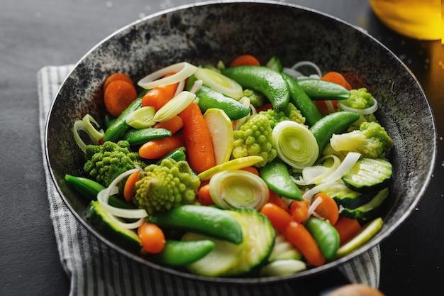 Verdure vegane in padella fritte o pronte per la cottura sul tavolo
