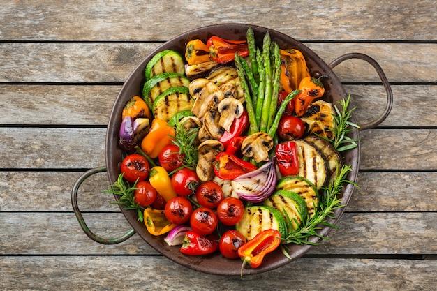 Concetto di cibo vegano, vegetariano, stagionale, estivo. verdure grigliate in padella su un tavolo di legno. sfondo piatto vista dall'alto